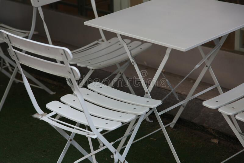 Biały lekki, zwijany metalowy stół i krzesła w letniej kafejce na zewnątrz obraz stock