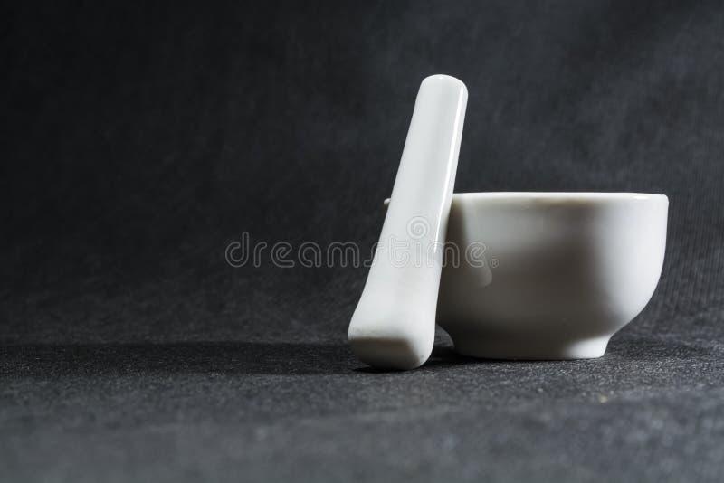 Biały moździerz z tłuczkiem od porcelany Pije puchar dla miażdżyć pikantność Czarny tło kaczki formularzowi kuchenni ładni poparc zdjęcie royalty free