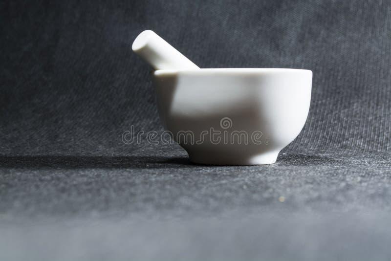 Biały moździerz z tłuczkiem od porcelany Pije puchar dla miażdżyć pikantność Czarny tło kaczki formularzowi kuchenni ładni poparc fotografia royalty free
