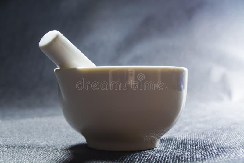 Biały moździerz z tłuczkiem od porcelany Pije puchar dla miażdżyć pikantność Czarny tło kaczki formularzowi kuchenni ładni poparc obrazy royalty free