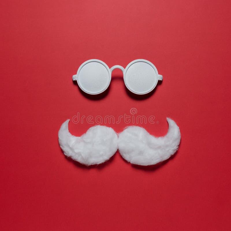 Biały modnisia wąsy Święty Mikołaj z okularami przeciwsłonecznymi na czerwonym tle zdjęcie royalty free