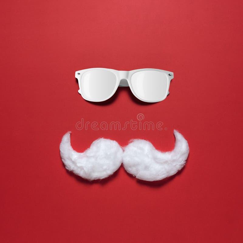 Biały modnisia wąsy Święty Mikołaj z okularami przeciwsłonecznymi na czerwonym tle zdjęcia stock