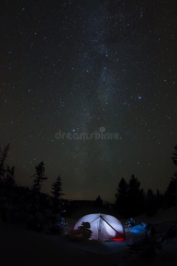 Biały namiot pod gwiaździstym niebem i milky sposób w drzewach w zim górach przy nocą zdjęcia stock