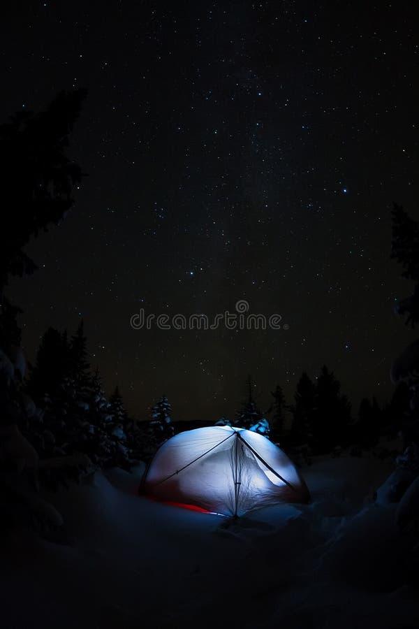Biały namiot pod gwiaździstym niebem i milky sposób w drzewach w zim górach przy nocą zdjęcia royalty free
