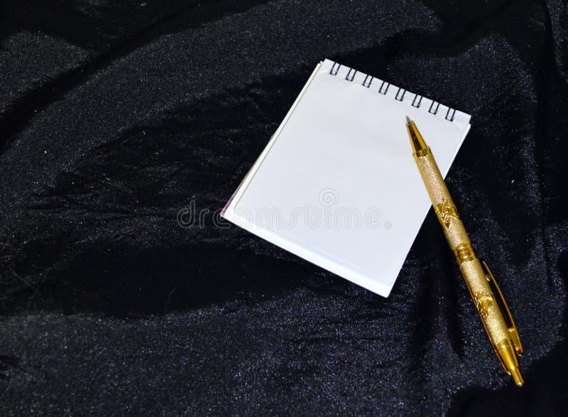 Biały notatnik z złotym piórem na czarnym tle fotografia royalty free