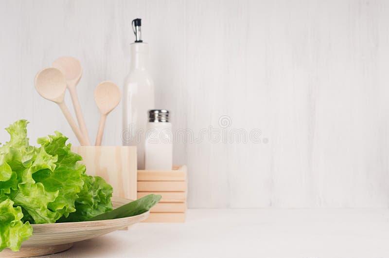 Biały nowożytny kuchenny wystrój z beżowym naturalnym drewnianym naczyniem, naczynia, świeża zielona sałatka na drewnianym tle obrazy stock