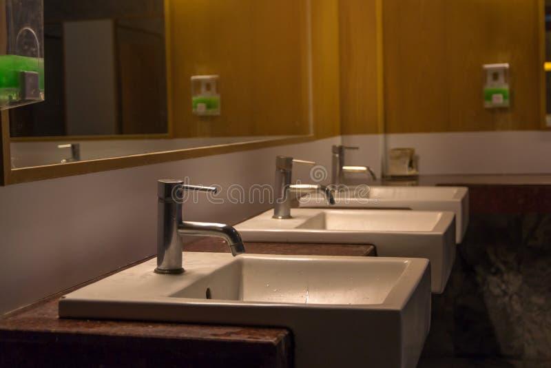 Biały obmycie pucharu rząd w nowożytnym toalety wnętrzu, obmycie basenu tło obraz royalty free
