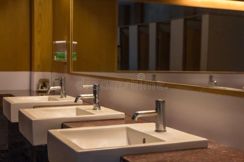 Biały obmycie pucharu rząd w nowożytnym toalety wnętrzu, obmycie basenu tło obrazy royalty free