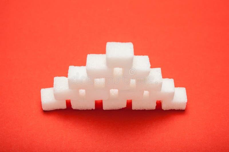 Biały ostrosłup sześciany cukier na czerwonym tle zdjęcie royalty free