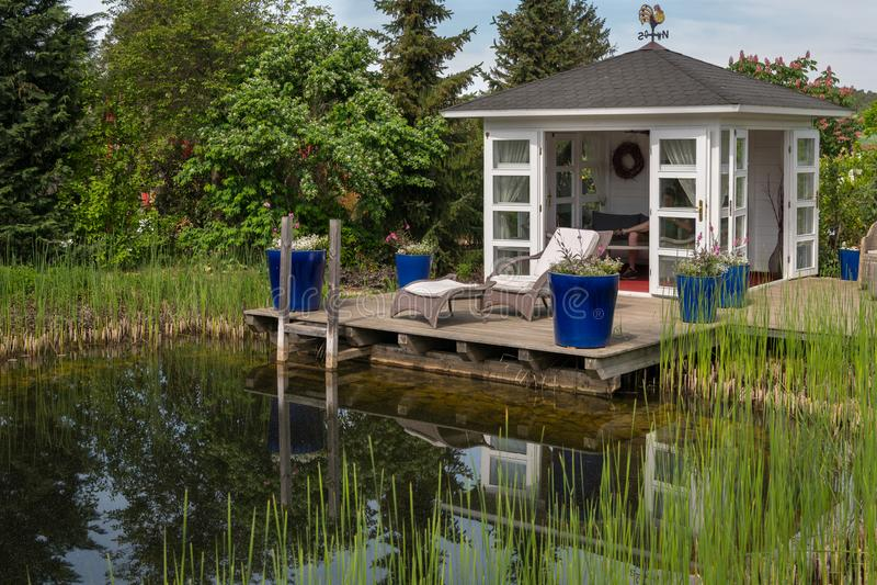 Biały pawilon i tarasowy pobliski staw w ogródzie zdjęcia royalty free