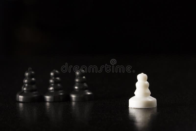 Biały pionek stoi out wśród czerni na ciemnym tle obraz stock