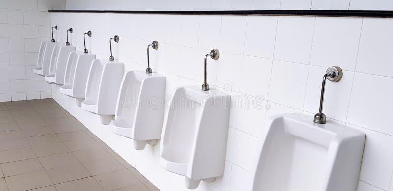 Biały pisuar na biel ścianie w mężczyznach jawna toaleta, washroom lub toaleta, obraz royalty free