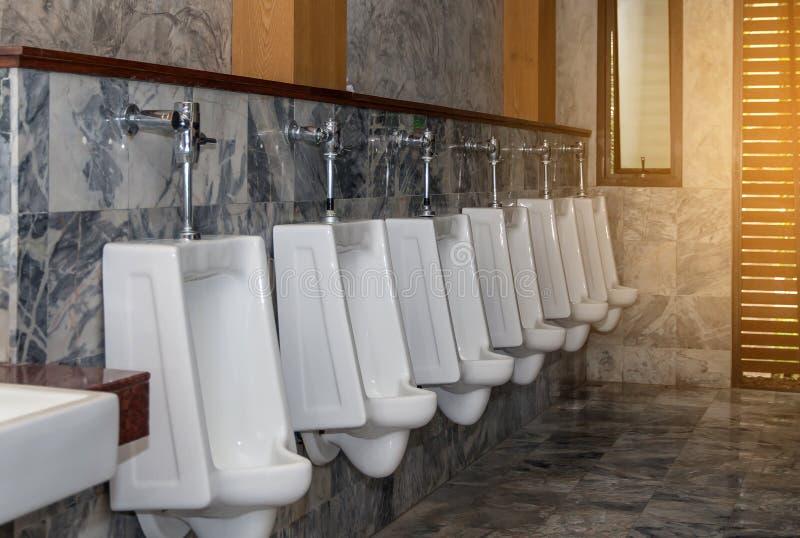 Biały pisuaru rząd w nowożytnym toalety wnętrzu, pisuaru tło obraz royalty free