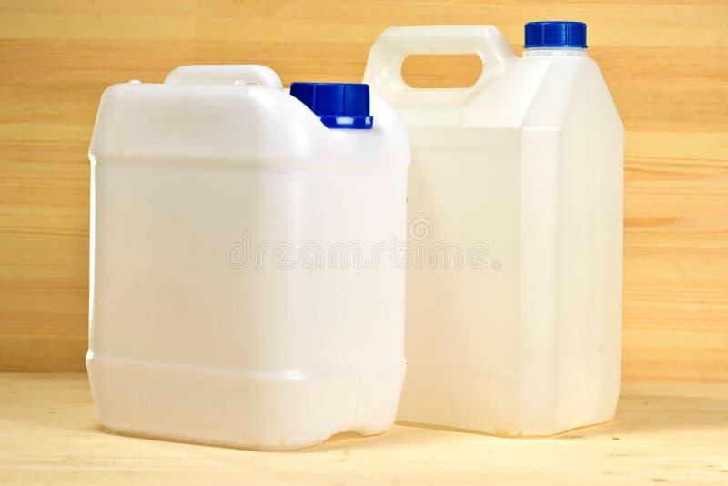 Biały plastikowych zbiorników galon na tle drewniany wa zdjęcie stock