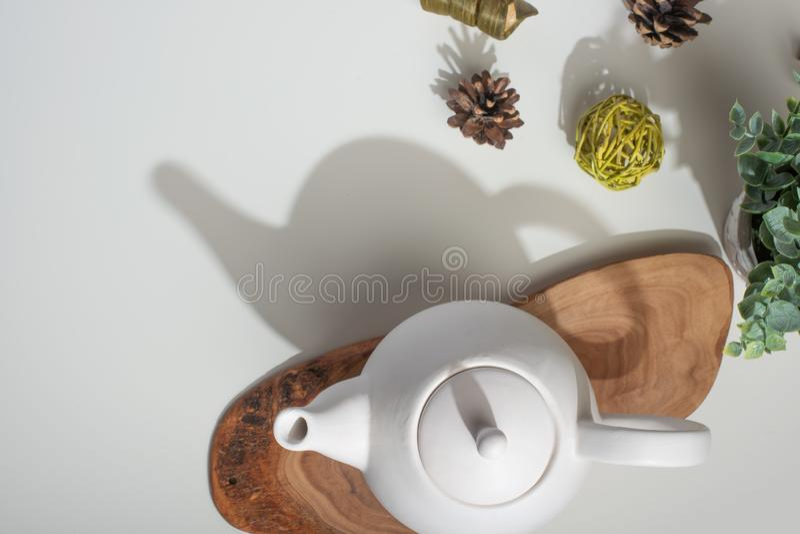 Biały porcelany teapot z akcesoriami na drewnianej desce na białym stole na widok kosmos kopii fotografia stock