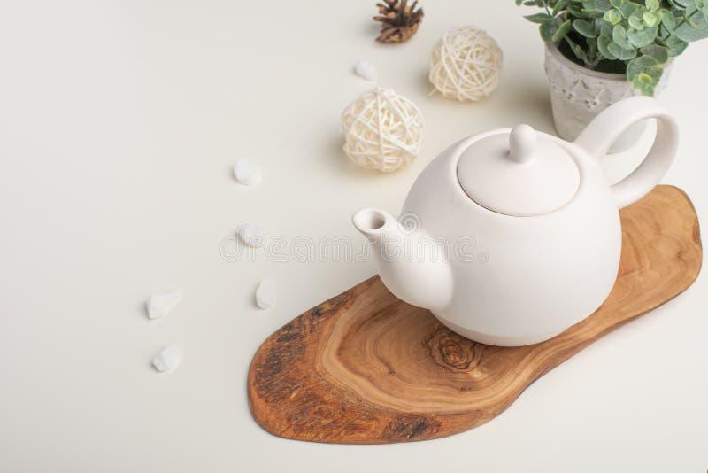 Biały porcelany teapot z akcesoriami na drewnianej desce na białym stole na widok kosmos kopii obraz stock