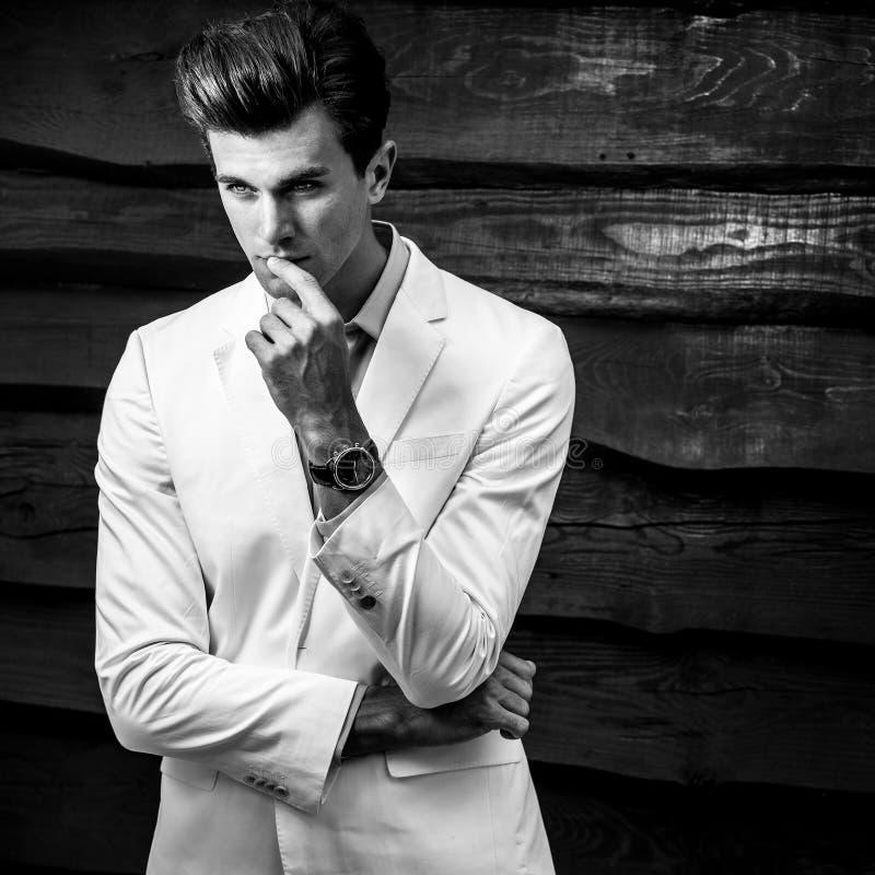 Biały portret młody przystojny modny mężczyzna w białym kostiumu przeciw drewnianej ścianie zdjęcia stock