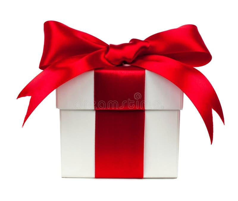 Biały prezenta pudełko z czerwonym łękiem i faborek nad bielem fotografia stock