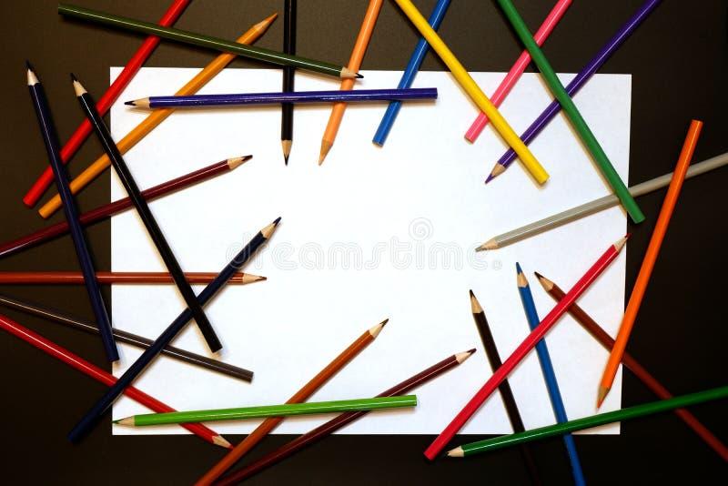 Biały prześcieradło papier i niektóre barwioni ołówki wokoło go zdjęcia royalty free