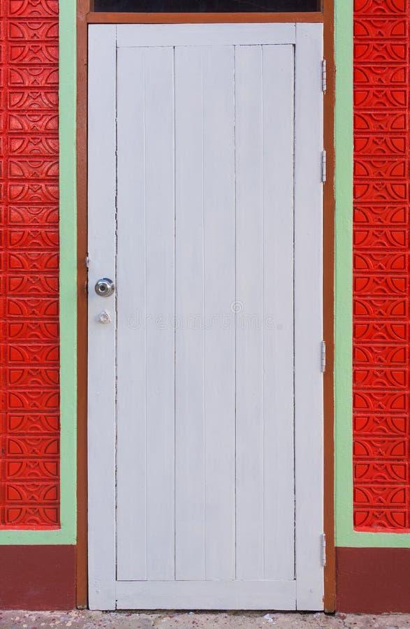 Biały rocznika drzwi i pomarańczowy kolor malujemy ściana z cegieł zdjęcie royalty free