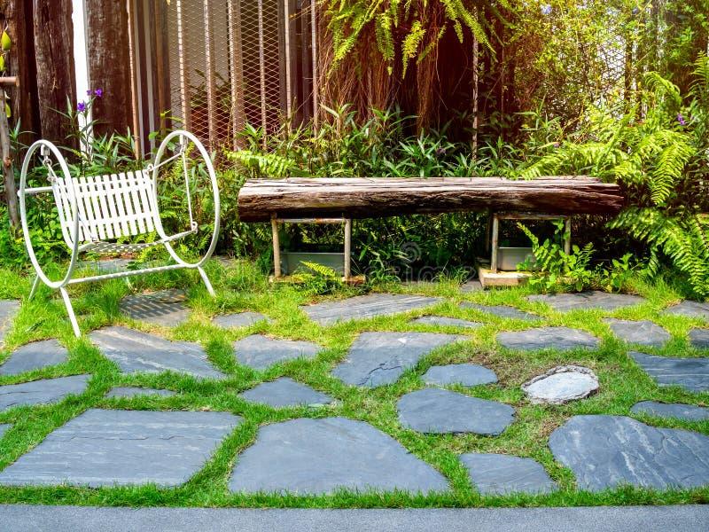 Biały rocznika ogródu huśtawki siedzenie na kamiennej podłodze w zielonym ogródzie obrazy stock