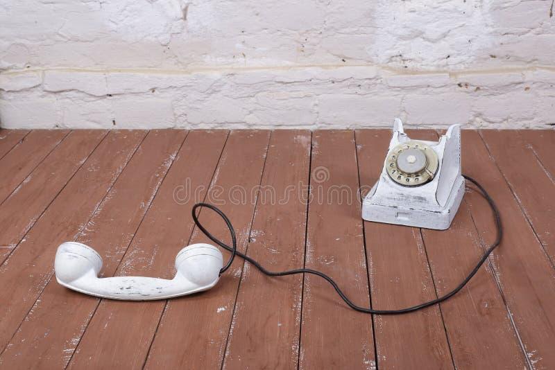 Biały rocznika telefon z w górę bielu ściennego tła i drewna dalej obrazy royalty free