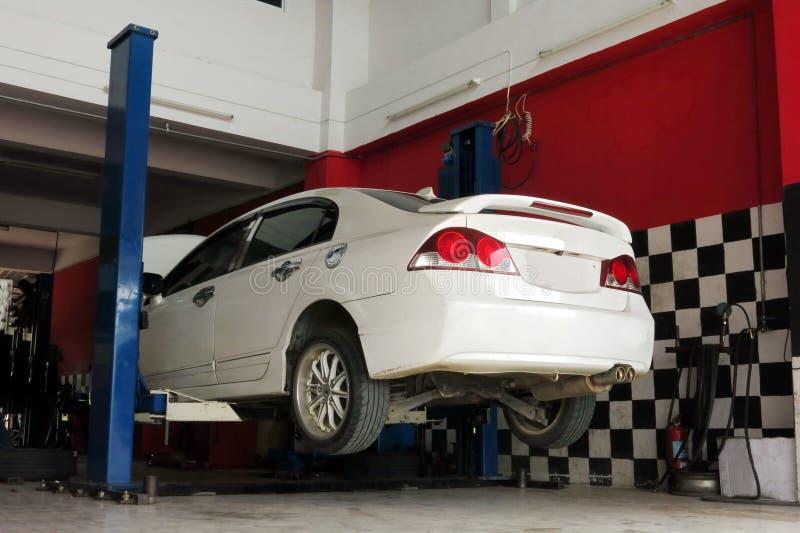 Biały samochód podnosi w górę naprawianie procesu przy garażem dla zdjęcia stock