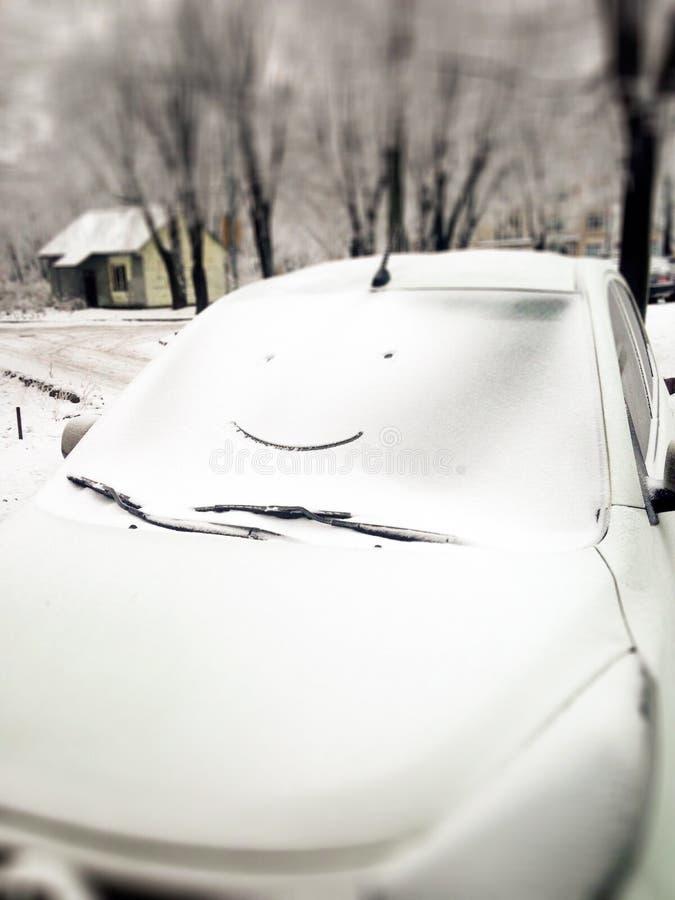 Biały samochód w śniegu z rysunkową smiley twarzą na okno Szczęśliwy i śmieszny zimy tło Śnieżny uśmiech na samochodowym szkle zdjęcia stock