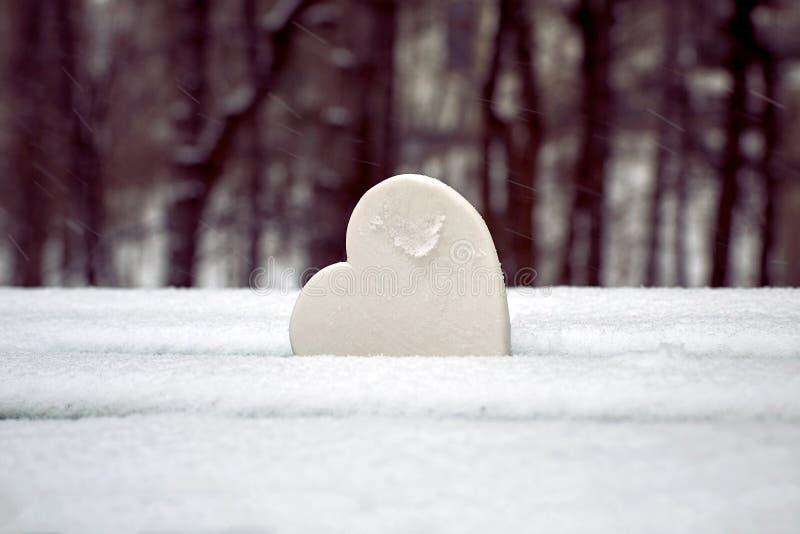 Biały serce na śnieżystej parkowej ławce czysty znak miłości fotografia stock