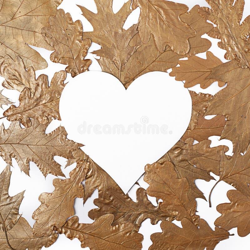 Biały serce na kreatywnie przygotowania złoci liście obrazy stock