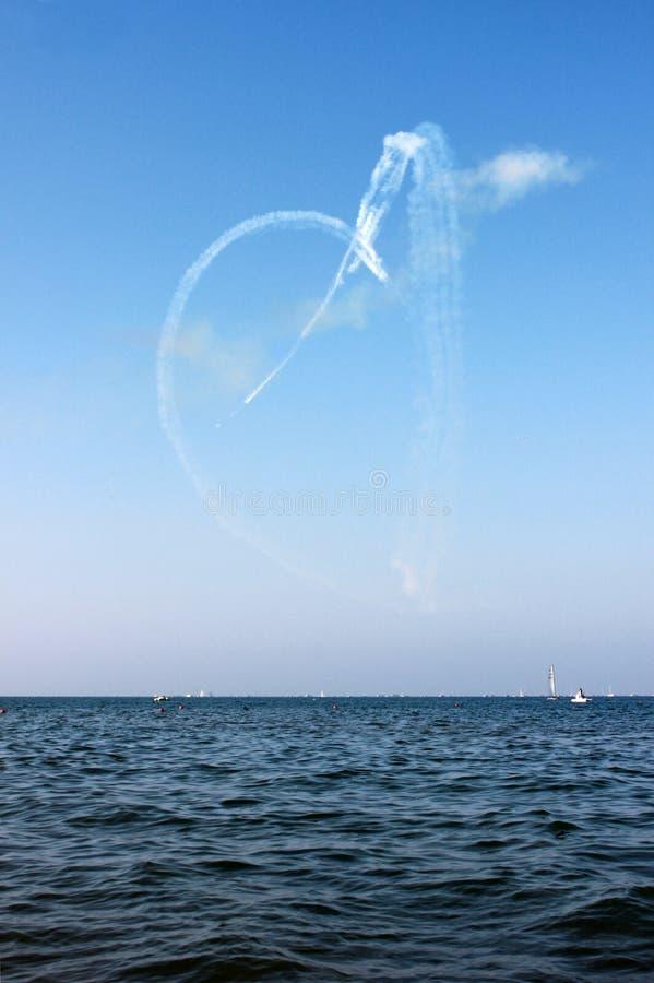 Biały serce tonie samolotem i morzem na niebieskiego nieba tle, pionowo widok obraz stock