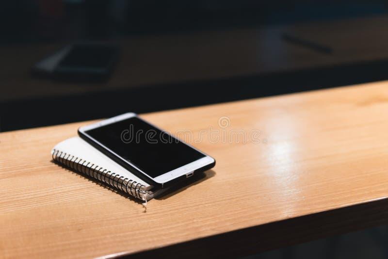 Biały smartphone, notatnik drewniany stół w kawiarni, Freelancer pracuje daleko Online marketing, edukacja dla adulte Nocy miasto obraz stock