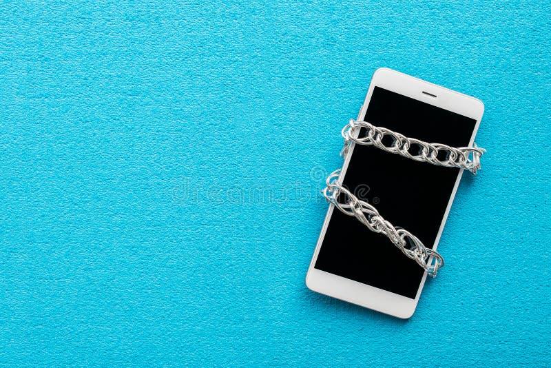 Biały smartphone z metalu łańcuchem na błękitnym tle Digital de zdjęcia stock