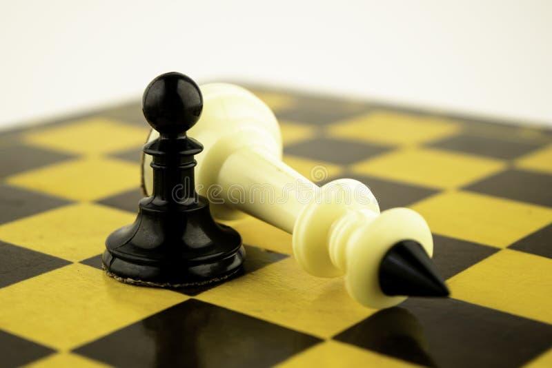 Biały smoka królewiątko szachy kłama na chessboard blisko czarnego pionka pojęcie fotografia stock