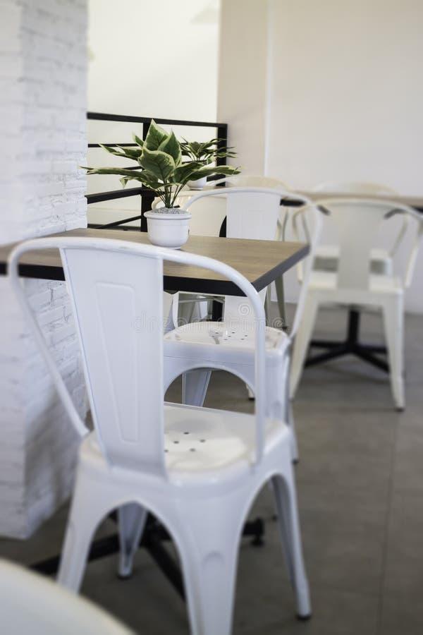 Biały stalowy krzesło i drewniany stół zdjęcia stock