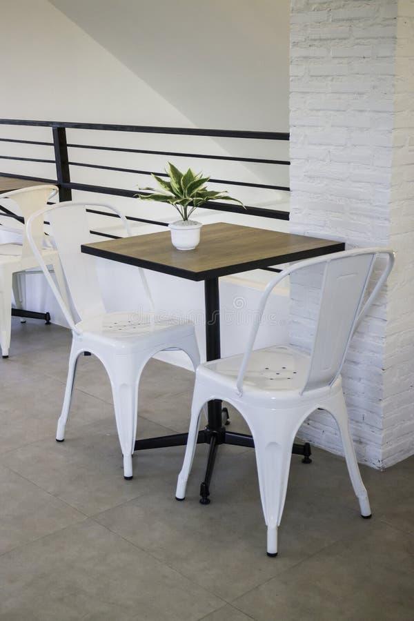 Biały stalowy krzesło i drewniany stół obraz stock