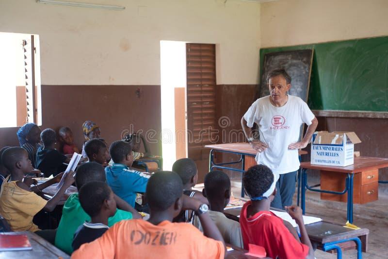 Biały starszy mężczyzna uczy czarnych dzieci w Afryka zdjęcie royalty free