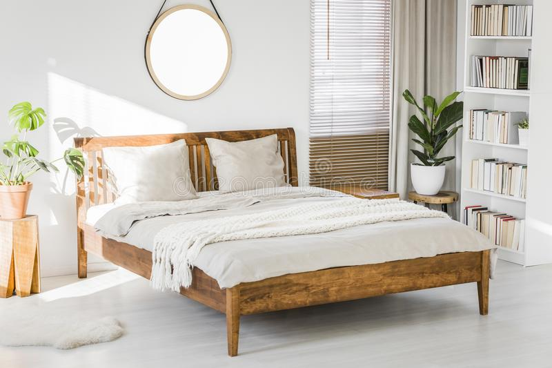 Biały sypialni wnętrze z drewnianym rozmiaru łóżkiem, świeża zieleń pl fotografia royalty free
