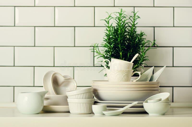 Biały tableware dla słuzyć Naczynia, filiżanki, łyżki, naczynia i inny różny biały materiał na blacie, Kuchnia zdjęcia royalty free