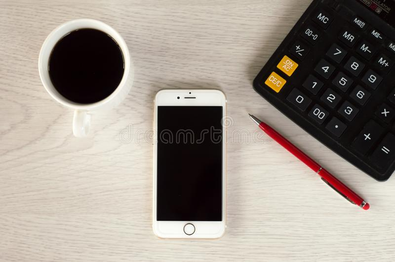 Bia?y telefon z fili?anka kawy, czerwony pi?ro i kalkulator, k?amamy na bia?ym drewnianym stole zdjęcie royalty free