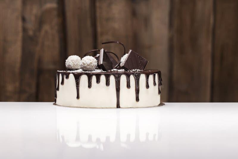 Biały tort zakrywający z czekoladowym glazerunkiem, dekorującym z ciemnymi czekoladowymi i kokosowymi cukierkami z białą czekolad zdjęcia royalty free