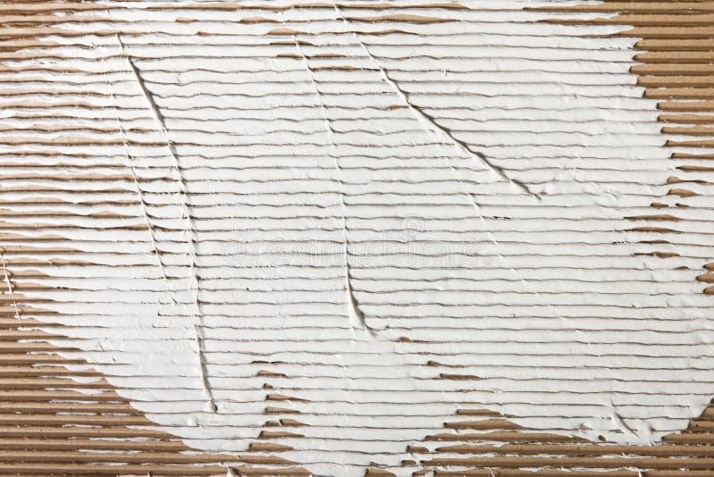 Biały tynk rozprzestrzeniający na kartonowym tle zdjęcia stock