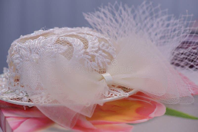 Biały upiększony kapeluszowy odpoczywać na kwiaciastym płótnie, staromodny kobiety ` s ślubny akcesorium fotografia stock