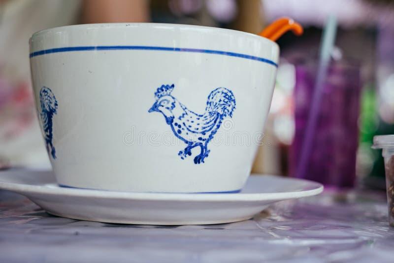 Biały wielki puchar z tajlandzkim kurczaka wzorem na stole fotografia royalty free