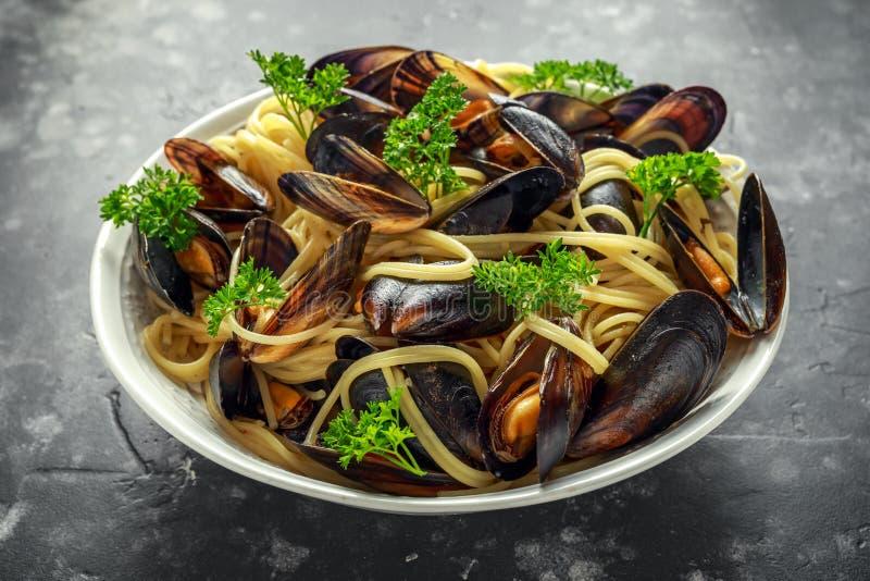 Biały wino i czosnki dekatyzujący mussels z makaronem słuzyć z pietruszką obrazy royalty free