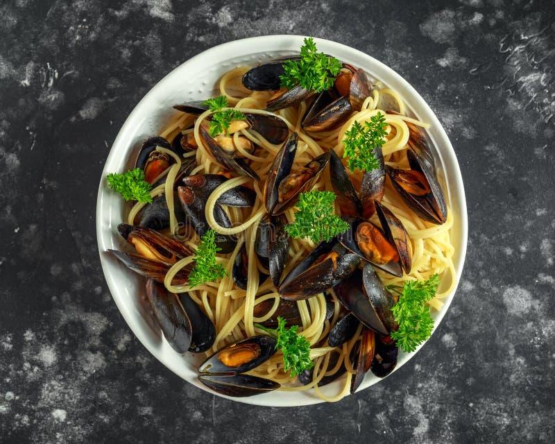 Biały wino i czosnki dekatyzujący mussels z makaronem słuzyć z pietruszką fotografia stock
