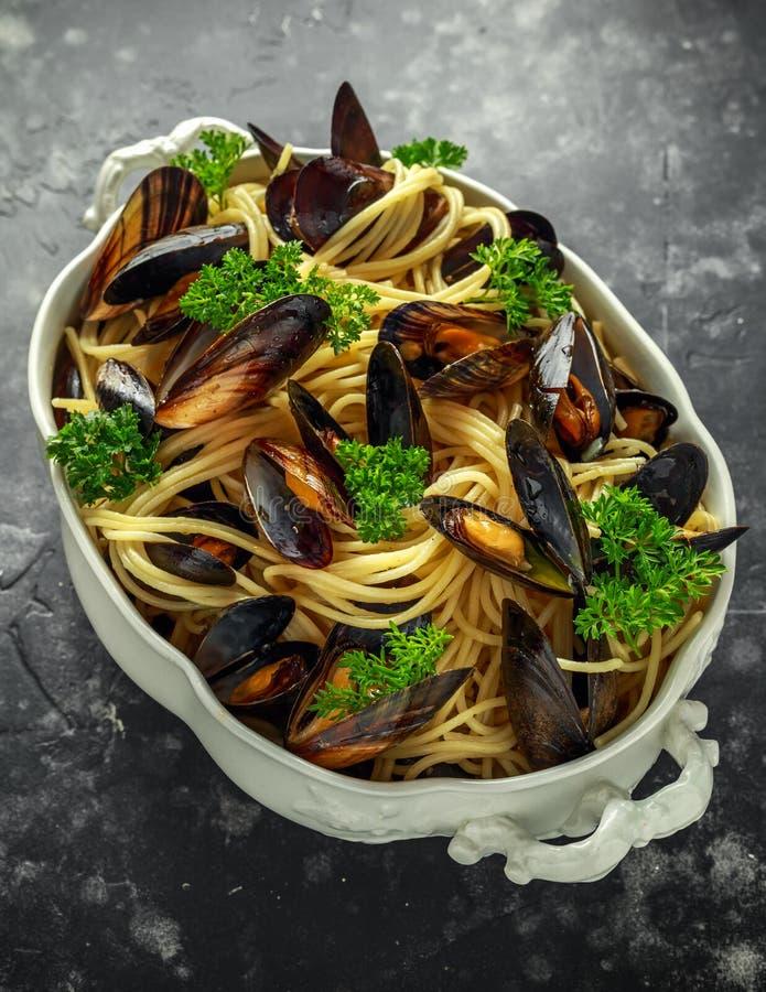 Biały wino i czosnki dekatyzujący mussels z makaronem słuzyć z pietruszką w białym rocznika tureen obraz royalty free