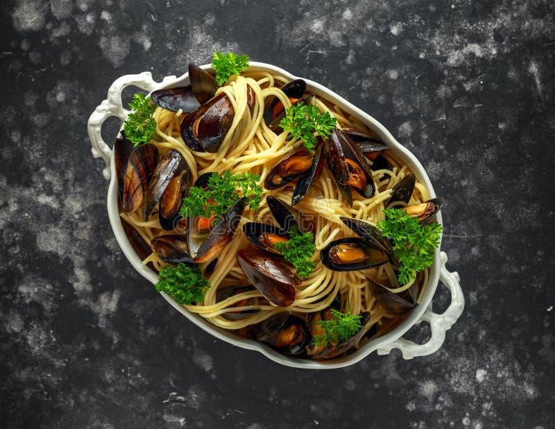 Biały wino i czosnki dekatyzujący mussels z makaronem słuzyć z pietruszką w białym rocznika tureen fotografia stock