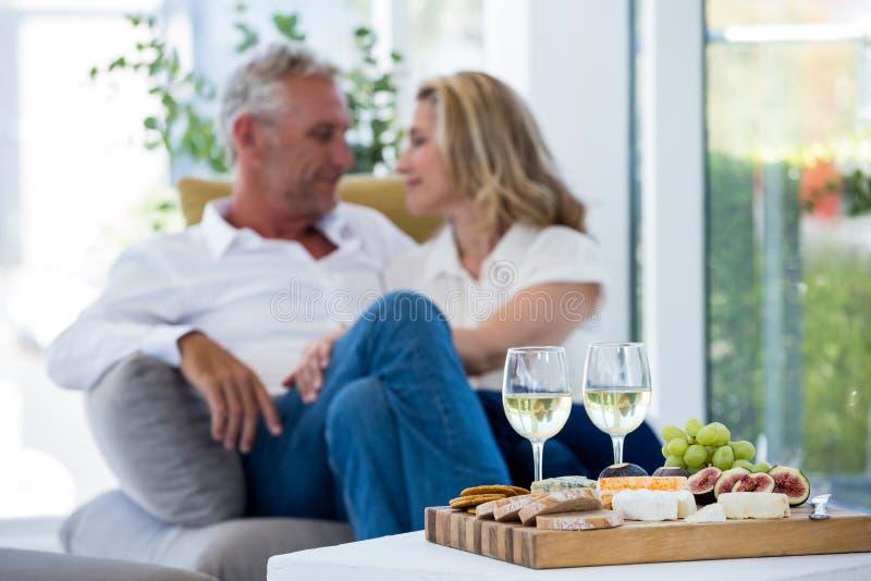 Biały wino i jedzenie na stole z romantyczną parą obraz stock