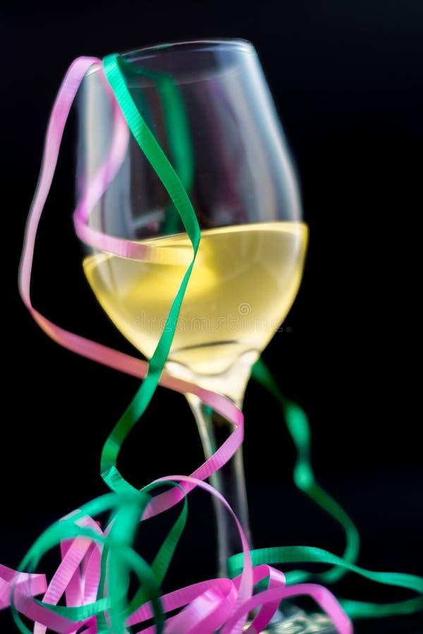 Biały wino w szkle z faborkami i czarnym tłem obrazy stock